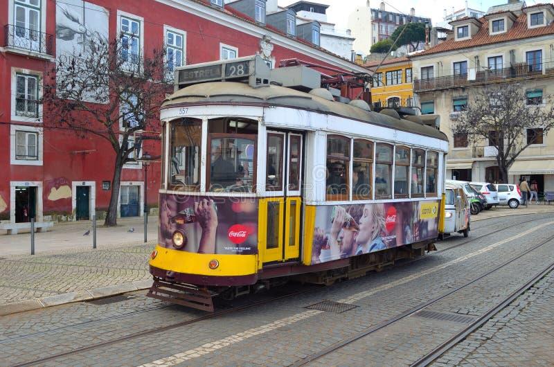 Traditional old yellow Lisbon tram on Largo das Portas do Sol. royalty free stock photo