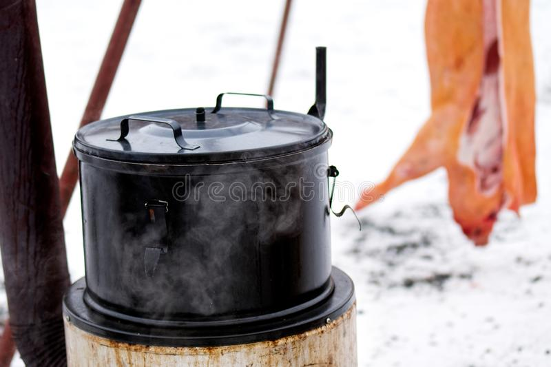 Traditional outdoor Czech pig slaughter in winter. Large steaming emanel pot.  royalty free stock photography