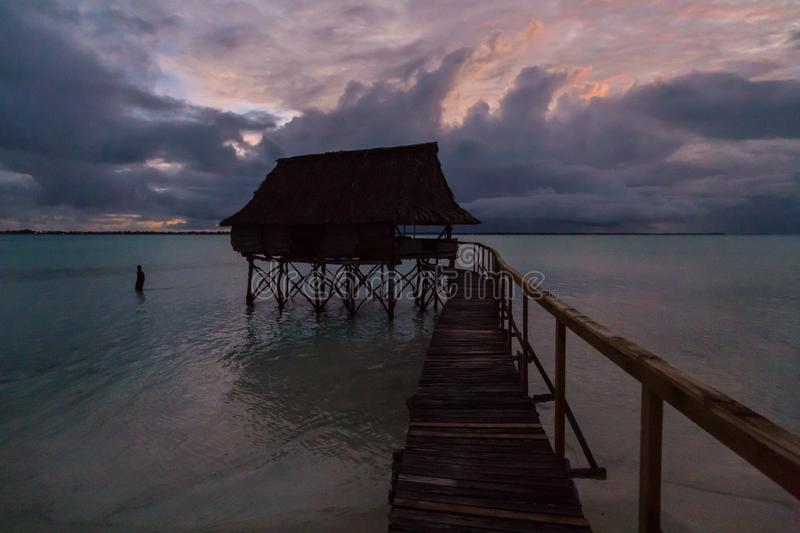 Traditional overwater thatched roof bungalow hut in lagoon of South Tarawa atoll, night, evening, twilight, sunset, Kiribati,. Traditional authentic overwater stock photos