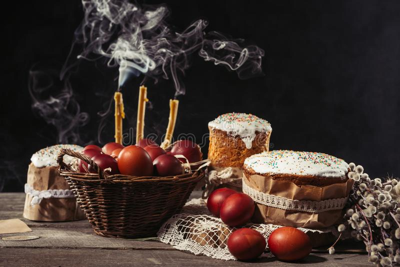 View of painted eggs in basket, willow twigs and delicious easter cakes. Traditional painted chicken eggs, candles with smoke and easter cakes with catkins on stock photography
