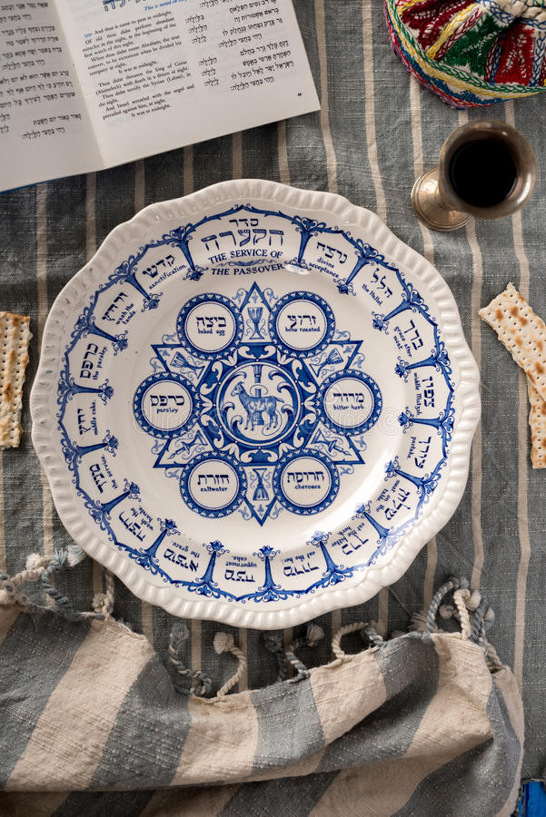Traditional Passover Plate. Vintage traditional passover plate, used during the Jewish holiday is show with the habbadah, kiddush cup and colourful yarmulke or royalty free stock photography
