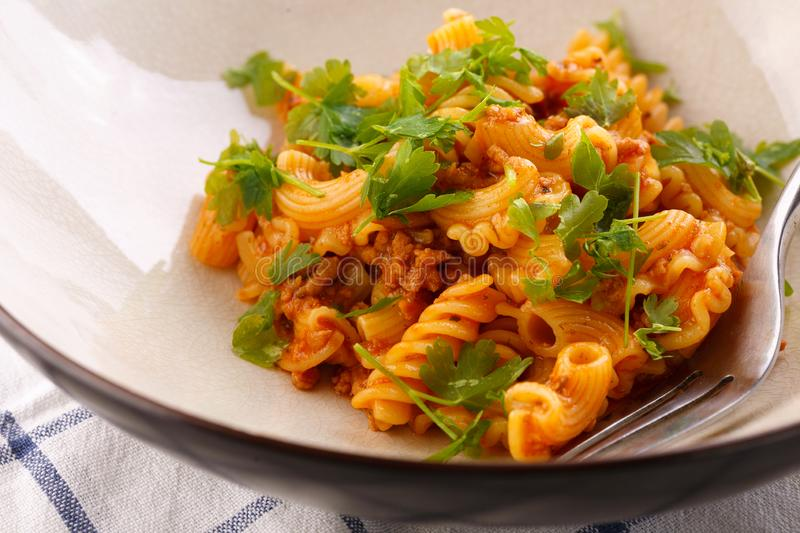 Traditional pasta with meat and herbs in a beige plate stock photography