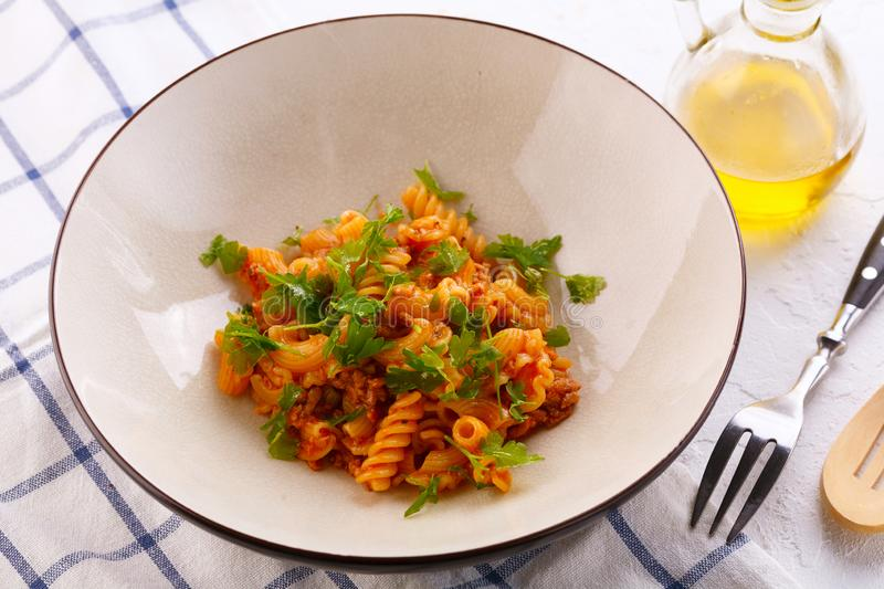 Traditional pasta with meat and herbs in a beige plate stock photos