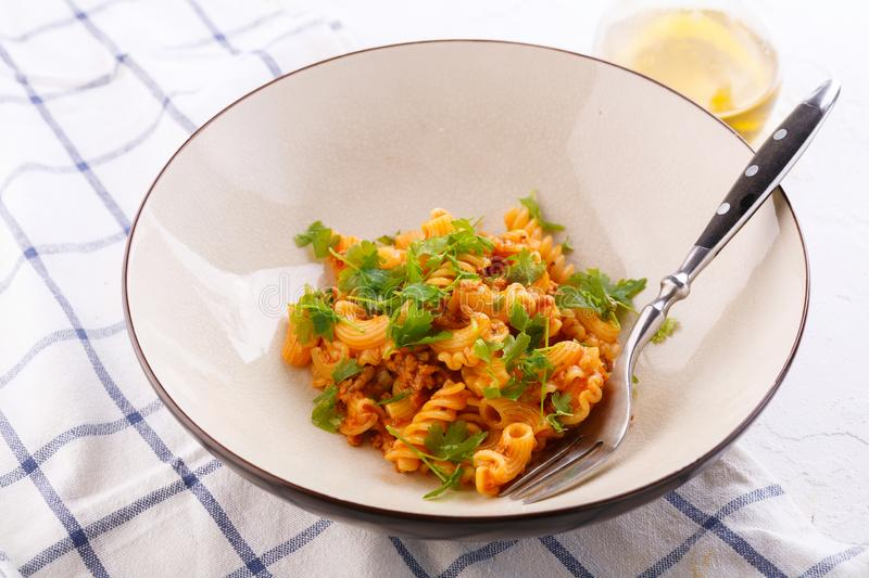 Traditional pasta with meat and herbs in a beige plate stock photo