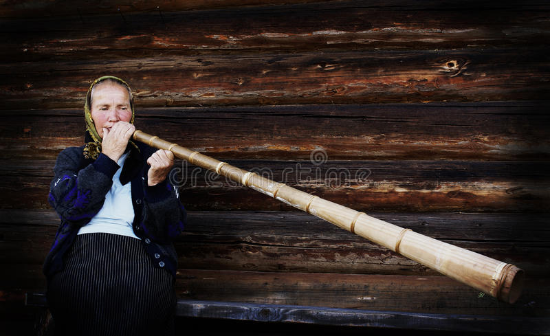 Traditional peasant playing a Bucium stock photo