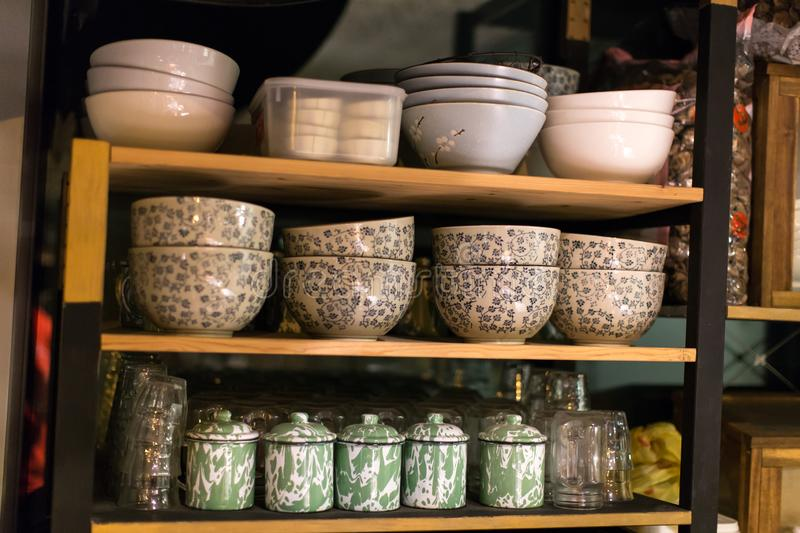 Peranakan Style Porcelain Dishware and Tin Cups. Traditional peranakan dishware style, including porcelain bowl and tin cups, displayed on a shelf in a local royalty free stock photo