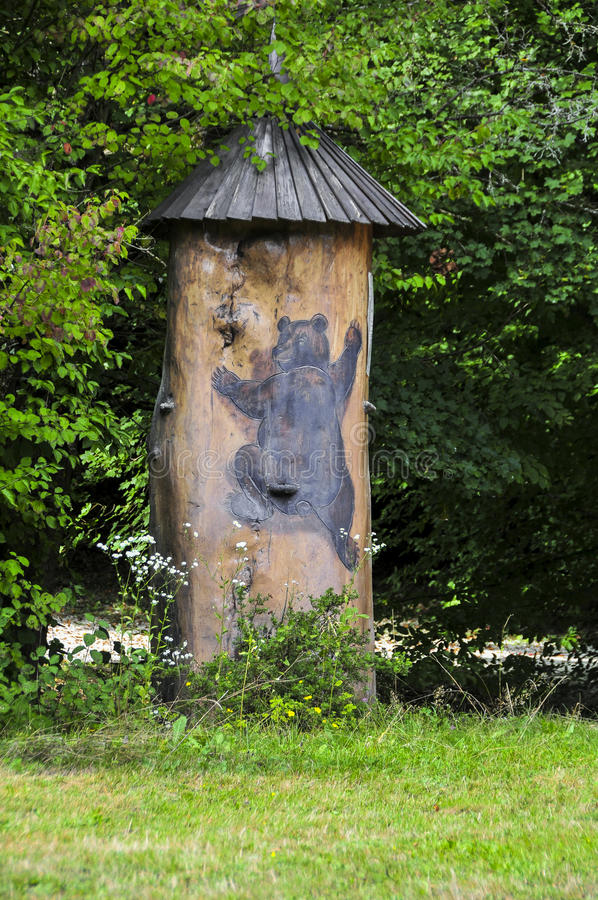 Traditional picturesque wooden bee hive in Slovenia, a tree trunk and painted bear. Traditional colorful and picturesque wooden bee hive made of tree trunk and a royalty free stock image