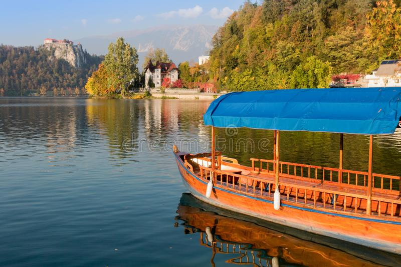Traditional pletna boat on the waters of Lake Bled with Bled Castle cliff on the background, Upper Carniola, Slovenia. Colorful. Autumn season royalty free stock photos