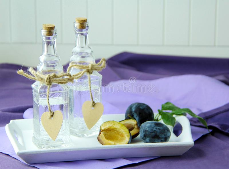 Traditional plum brandy in a glass carafe. Fresh plums on background. stock image