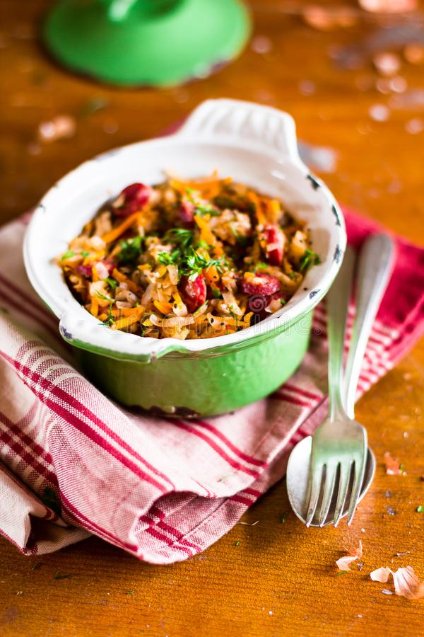 Traditional polish food. Bigos, stewed cabbage with carrot, onion, green lentil and pork meat sausages in a pot. On a wooden table, selective focus. German stock photos