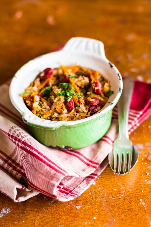 Traditional polish food. Bigos, stewed cabbage with carrot, onion, green lentil and pork meat sausages in a pot. On a wooden table, selective focus. German royalty free stock photography