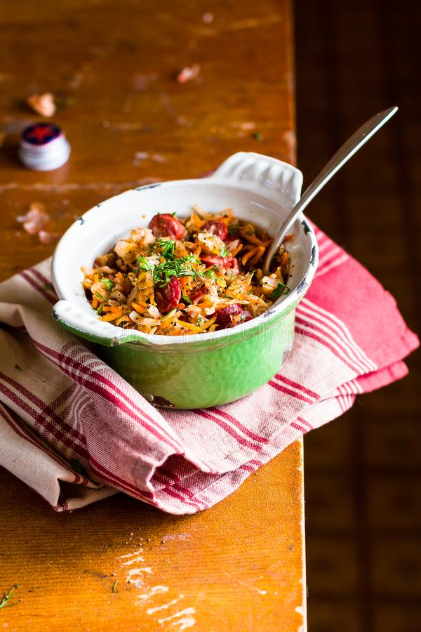 Traditional polish food. Bigos, stewed cabbage with carrot, onion, green lentil and pork meat sausages in a pot. On a wooden table, selective focus. German royalty free stock image
