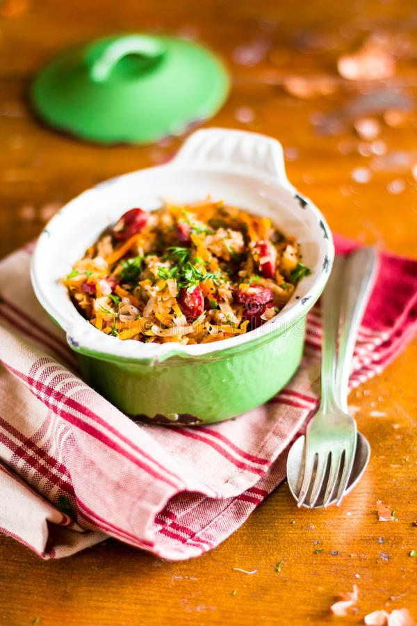 Traditional polish food. Bigos, stewed cabbage with carrot, onion, green lentil and pork meat sausages in a pot on a wooden table,. Selective focus. German stock image