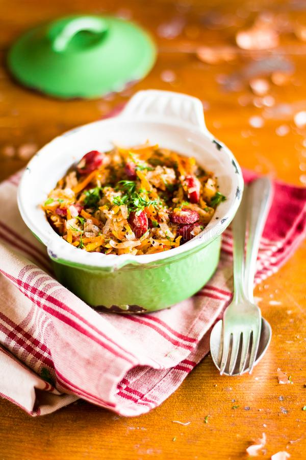 Traditional polish food. Bigos, stewed cabbage with carrot, onion, green lentil and pork meat sausages in a pot on a wooden table,. Selective focus. German stock photo