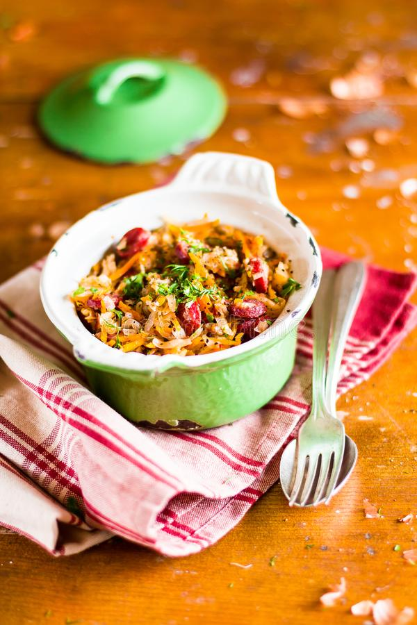 Traditional polish food. Bigos, stewed cabbage with carrot, onion, green lentil and pork meat sausages in a pot on a wooden table,. Selective focus. German royalty free stock photos