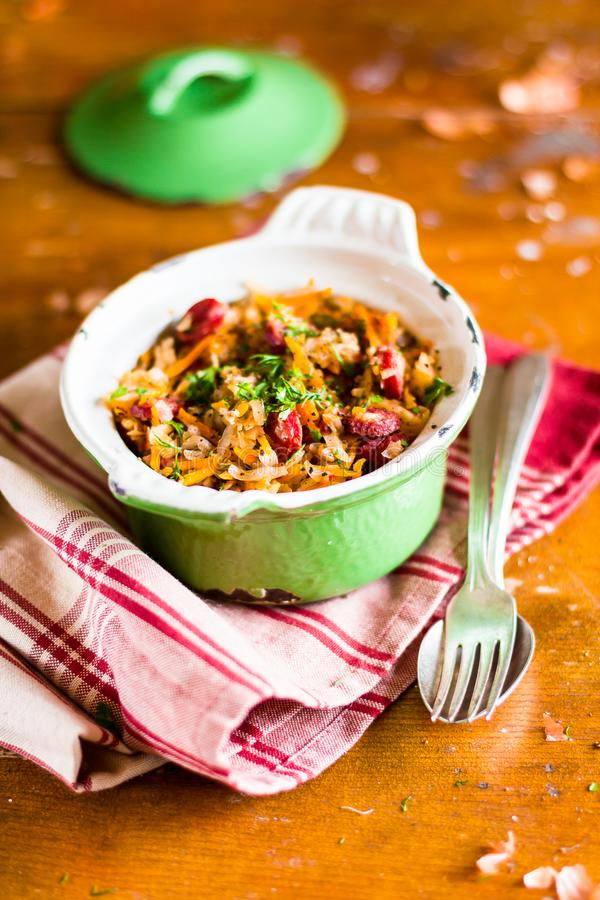 Traditional polish food. Bigos, stewed cabbage with carrot, onion, green lentil and pork meat sausages in a pot on a wooden table,. Selective focus. German stock photos