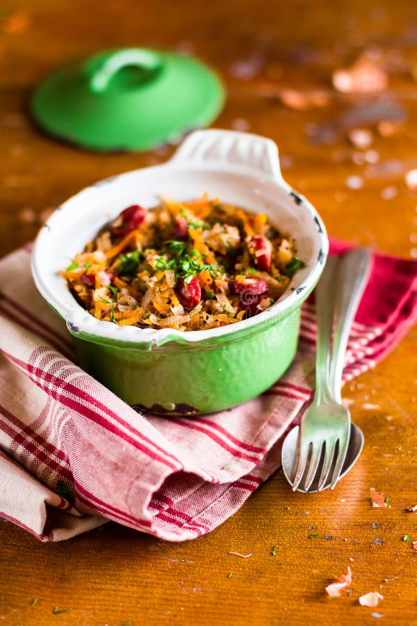 Traditional polish food. Bigos, stewed cabbage with carrot, onion, green lentil and pork meat sausages in a pot on a wooden table,. Selective focus. German royalty free stock image