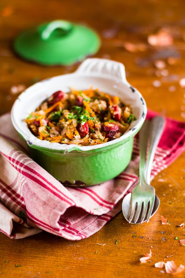 Traditional polish food. Bigos, stewed cabbage with carrot, onion, green lentil and pork meat sausages in a pot on a wooden table,. Selective focus. German stock images