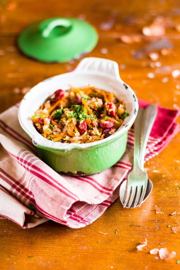 Traditional polish food. Bigos, stewed cabbage with carrot, onion, green lentil and pork meat sausages in a pot on a wooden table,. Selective focus. German royalty free stock photography