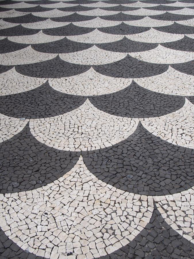 Traditional portugal black and white fish scale pattern tiled cobblestone sidewalk in funchal madeira royalty free stock images