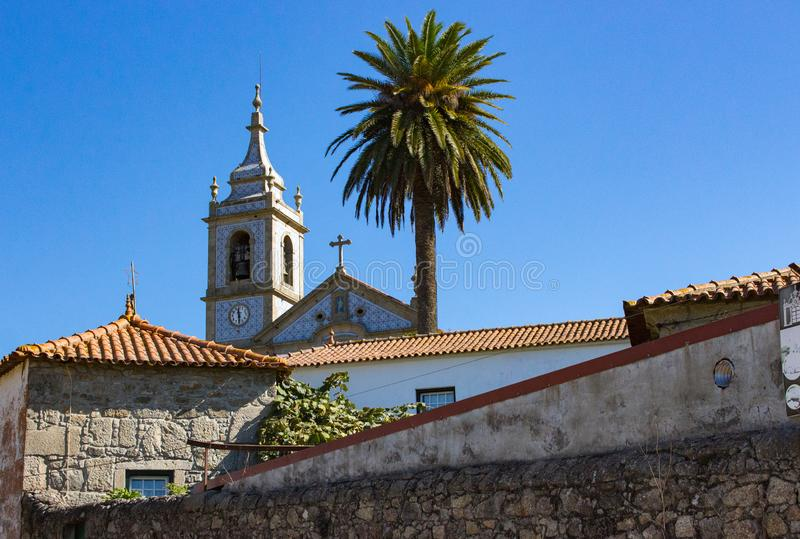 Traditional portuguese church with azulejos tiles with palm tree and old buildings. Mediterranean religious landmark. royalty free stock image