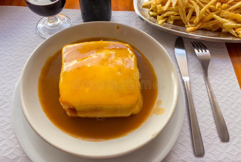 Traditional portuguese sandwich francesinha with glass of wine and fried potato. Francesinha in hot sauce with fork and knife. royalty free stock photography
