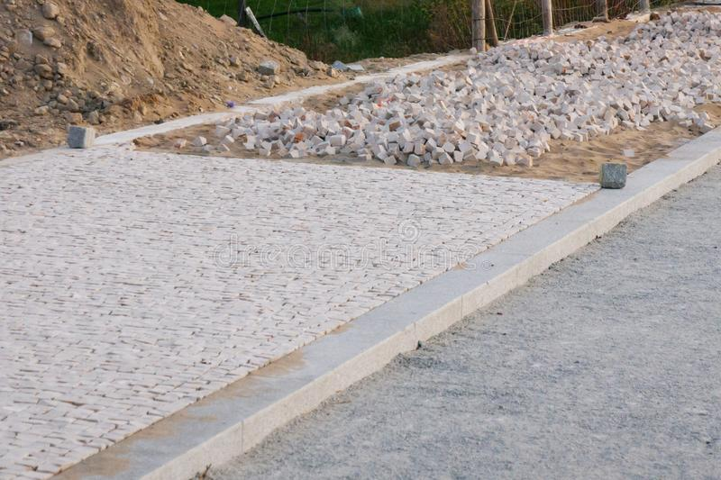 Traditional Portuguese sidewalk / pavement in construction with finished section in foreground and loose stones. With sand behind stock images