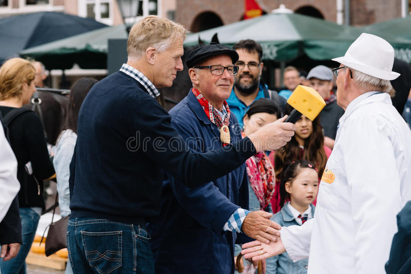 Traditional producers in Gouda Cheese Market a rainy day stock photography
