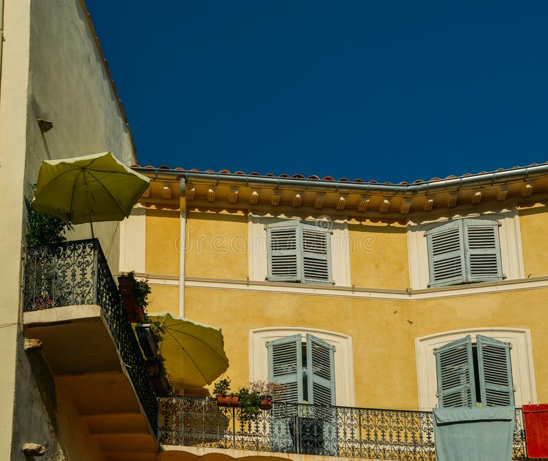 Traditional Provencal yellow facade with blue shutters stock photos