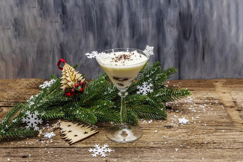Traditional prune dessert with nuts and whipped sour cream with sugar. New Year`s sweet treat concept. Wooden boards background. Traditional prune dessert with royalty free stock image