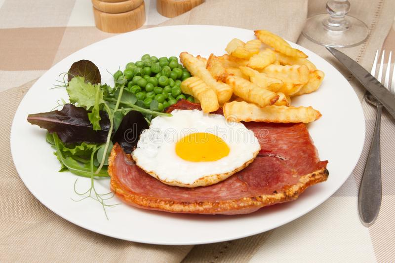 Gammon steak with a fried egg. A traditional pub lunch of gammon steak with a fried egg stock photography