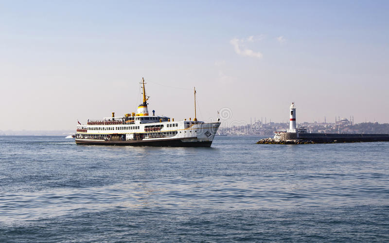 Traditional public ferry arriving. To Kadikoy station in Istanbul. Water breaker is also in the view. Hagia Sophia and Blue Mosque are in the background stock photo