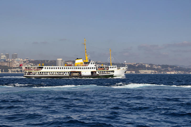Traditional public ferry crosses Bosphorus. From European to Asian side. It`s a sunny summer day in Istanbul. Besiktas area is in the view in the background stock image