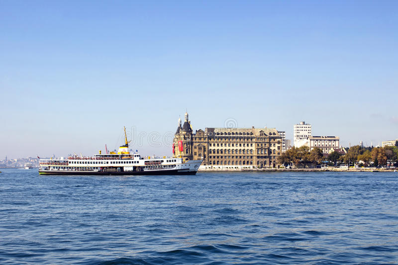 Traditional public ferry passes. By historical train terminal named Haydarpasa. Until 2012 the station was a major intercity, regional and commuter rail hub in stock image