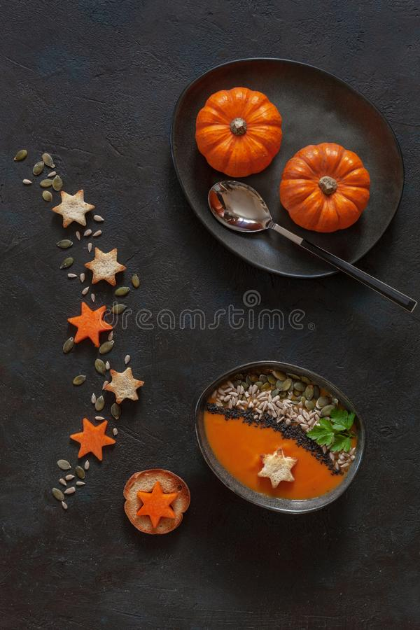 Traditional pumpkin homemade cream-soup with seeds, crackers stock photo