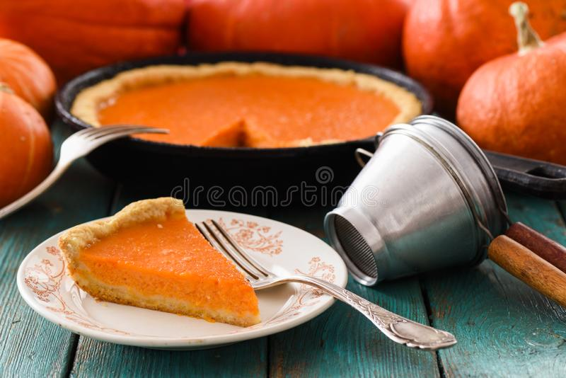 Traditional pumpkin pastry. Homemade bright colored pumpkin pie served with vintage sieves on blue background. Closeup royalty free stock photography