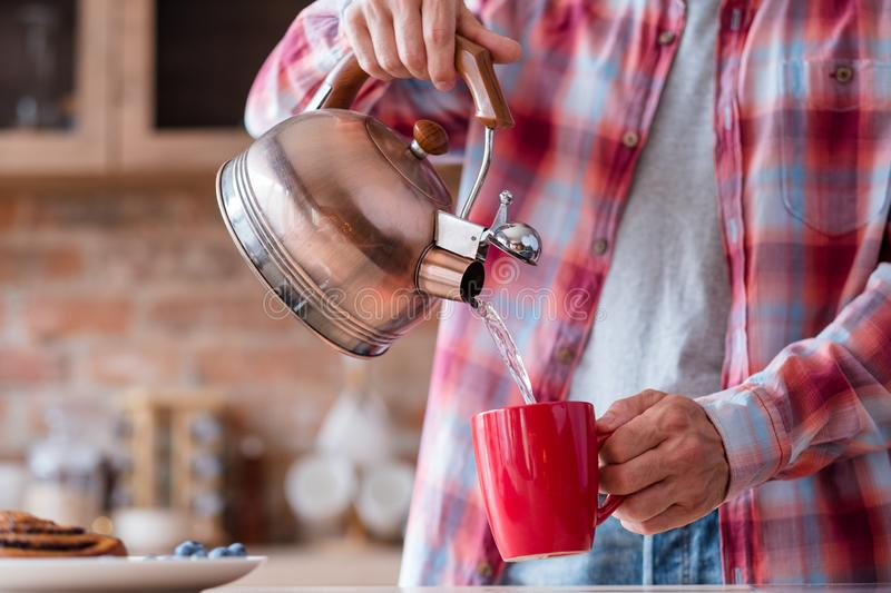 Breakfast tea pastry traditional food eating habit. Traditional quick breakfast of tea and pastry. food and eating habits concept. man pouring boiling water from stock photography