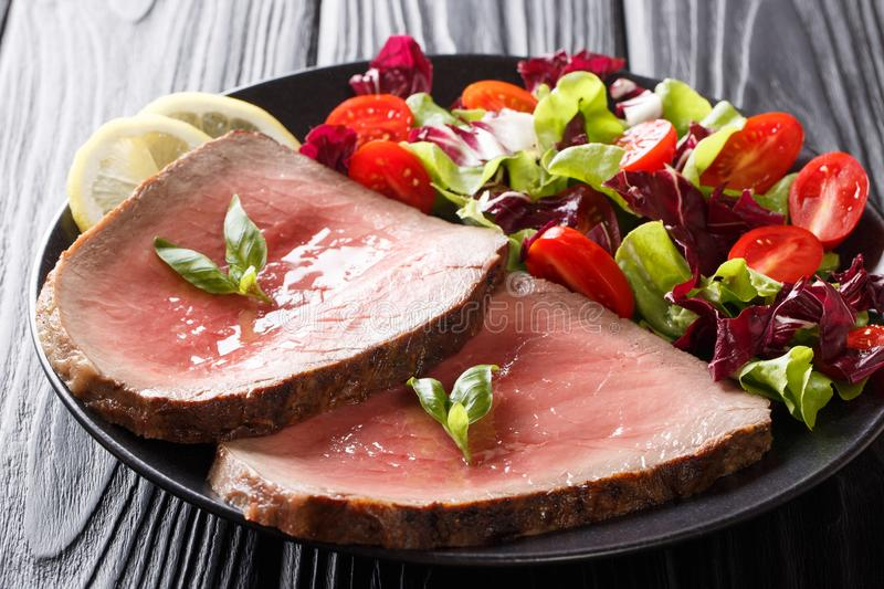Traditional recipe of beef steak is served with a summer vegetable salad close-up on a plate. horizontal. Traditional recipe of beef steak is served with a royalty free stock photography