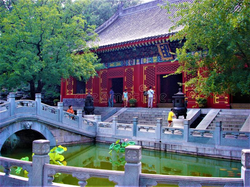 Traditional red building in China, nature, river, bridge, tourism and trees royalty free stock image