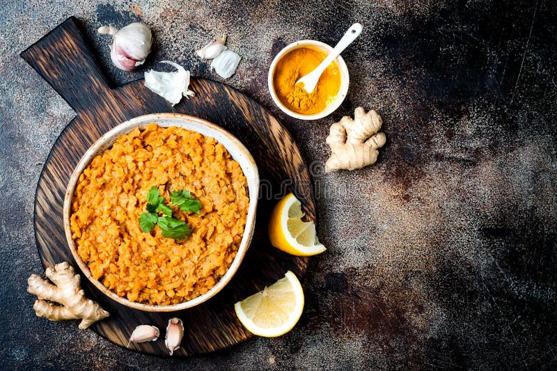 Traditional red lentil Dal. Indian Dhal spicy curry in bowl with flat bread and spices. Top view, overhead. royalty free stock photos