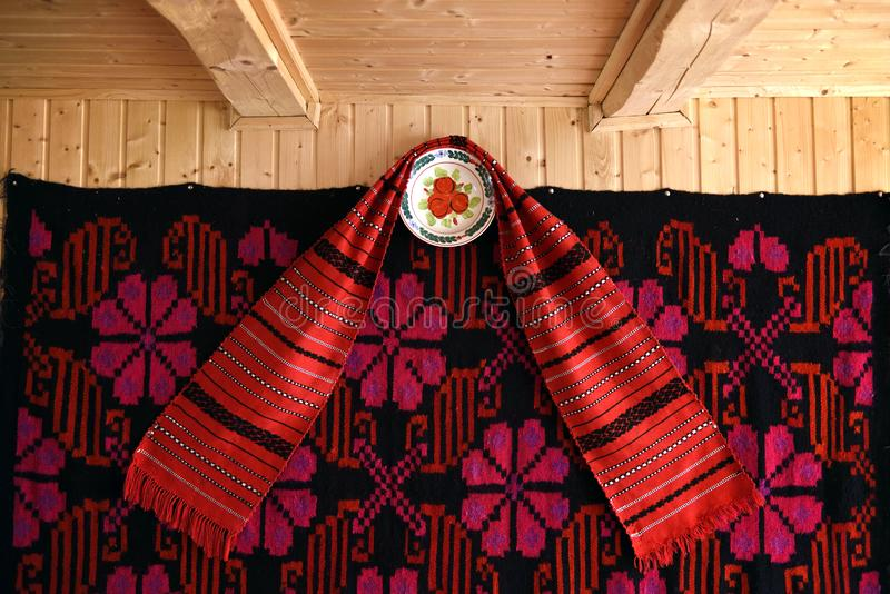 Traditional romanian towel and painted plates from Maramures, Romania. Traditional romanian towel and painted plates hanging on the wooden wall of traditional royalty free stock images