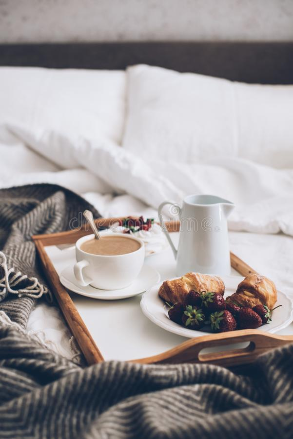 Traditional romantic breakfast in bed in white and beige bedroom royalty free stock images