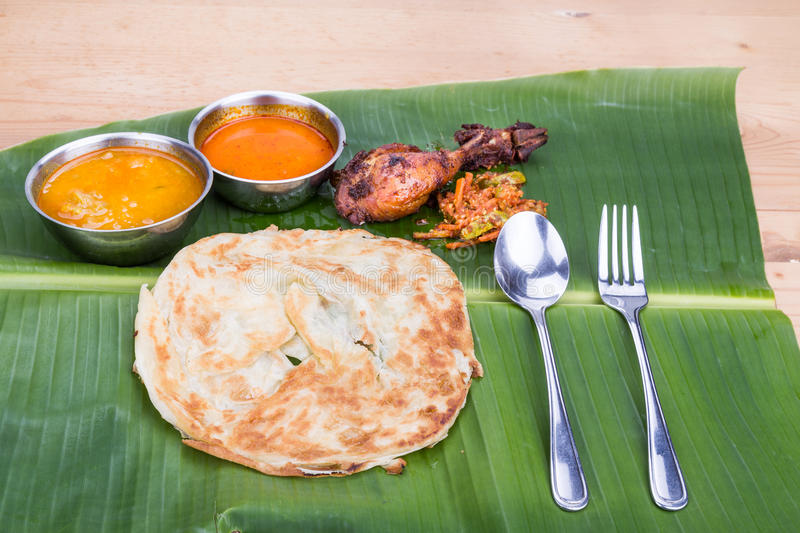 Traditional roti prata served on banana leaf with curry dhal. stock photography