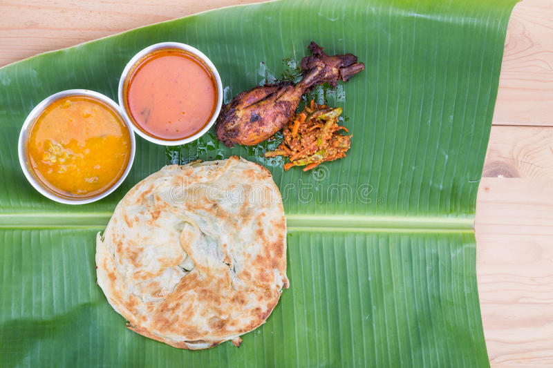 Traditional roti prata served on banana leaf with curry dhal. royalty free stock photo