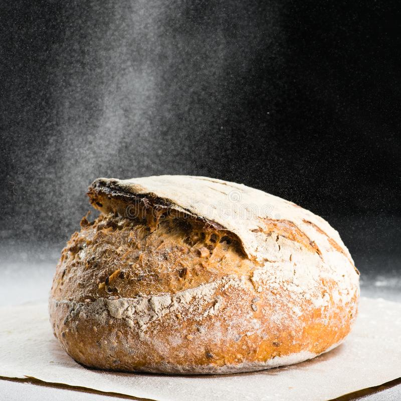 Traditional round artisan rye bread loaf with walnut and seeds w. As sprinkled flour on wooden cutting board. Dark background stock photos
