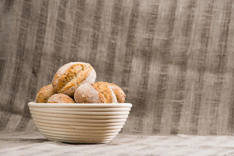 A traditional round artisan wheat bread loaves in a basket, text. Ile background. Rustic style stock image