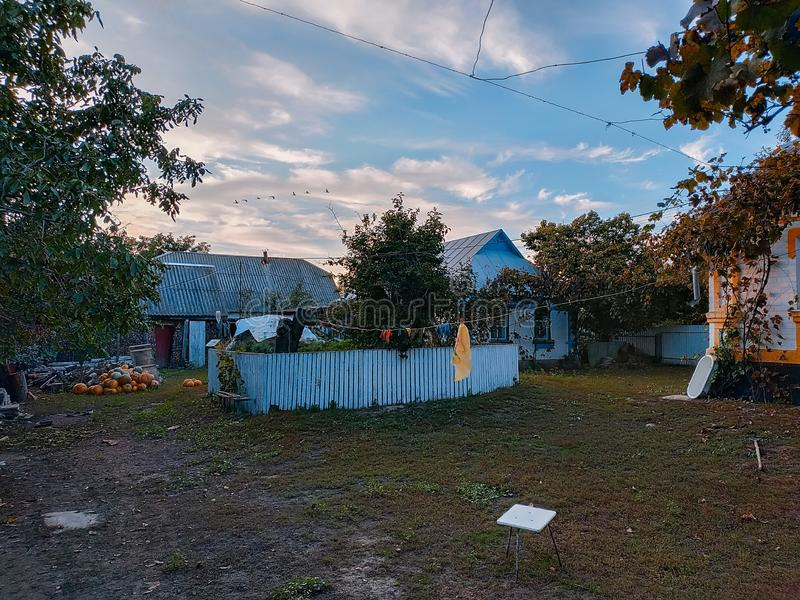 Traditional rural house and yard in village. View of traditional rural house and yard in village royalty free stock images