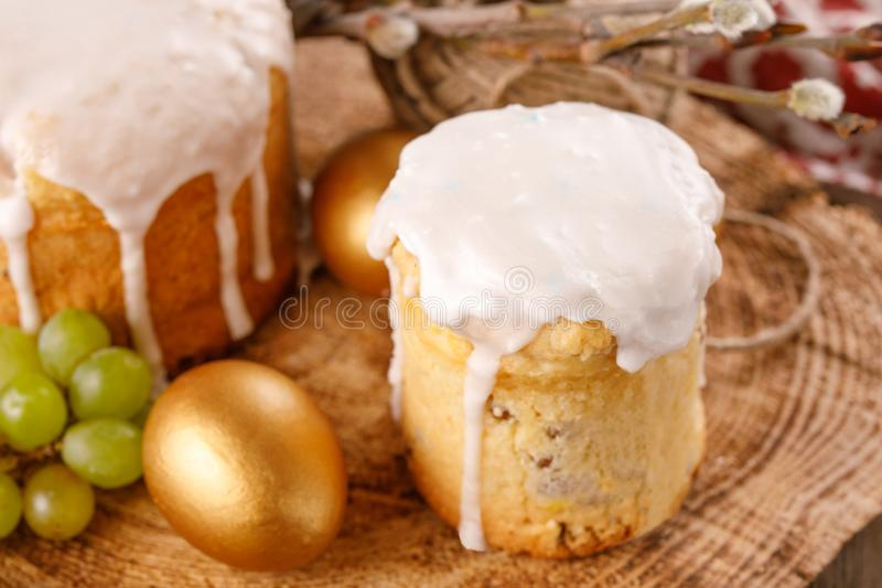 Traditional Russian Easter cakes kulich, with colored golden eggs on a wooden background. Close-up. Traditional Russian Easter cakes kulich, with colored golden royalty free stock photos