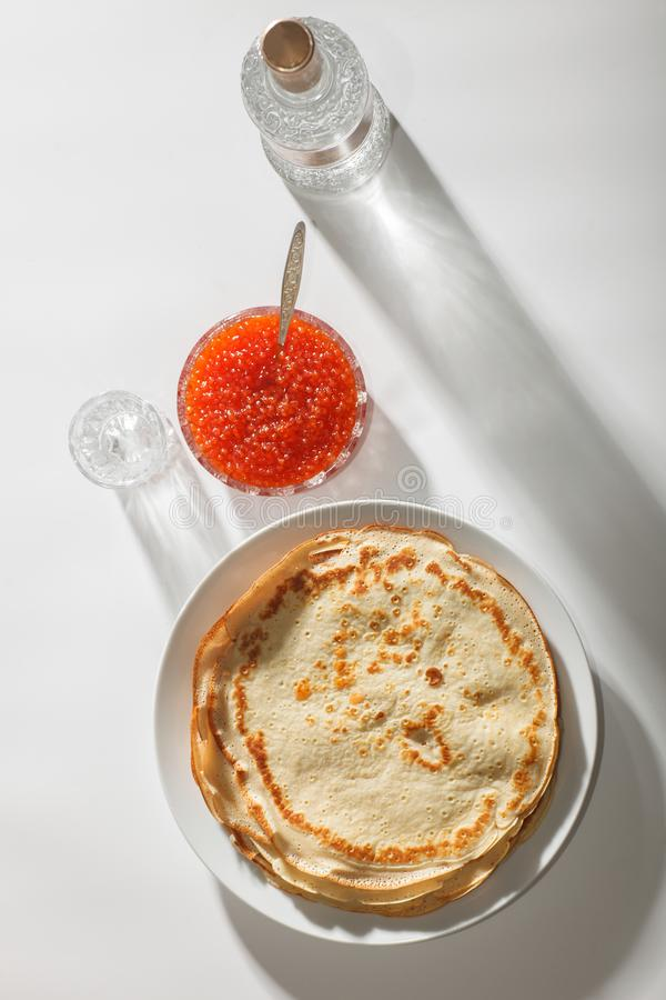 Crepes, red caviar and vodka. Traditional russian food - pancakes, red caviar, bottle of vodka on white table, minimalistic top view royalty free stock photography
