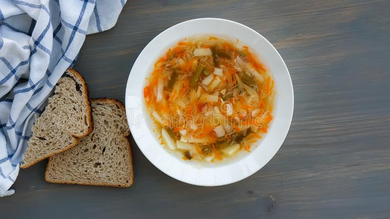 Traditional russian food. Soup shchi with sour cabbage in a white plate and bread on a gray background. Top view royalty free stock images